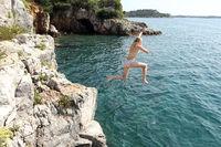 Mädchen springt ins blaue Meer