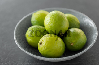 close up of whole limes in bowl on slate table top