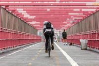 Man riding his bike in the cycling lane on Williamsburg Bridge, Brooklyn, New York City.