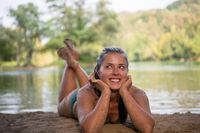 girl in a green bikini relaxing on the riverbank