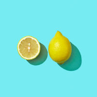 Fresh half and whole organic lemon on blue background with reflection of shadows and space for text. Ingredient for mojito. Top view