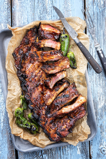 Barbecue spare ribs St Louis cut with hot honey chili marinade and jalapeno as top view in a rustic skillet and backing paper