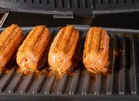 Plant based vegetarian sausages being grilled on griddle