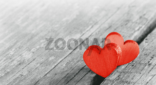 Two red hearts on old wood