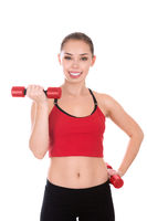 Portrait of young active woman doing exercise with dumbbells isolated over background
