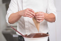 Professional confectioner making chocolate sweets at confectionery shop.