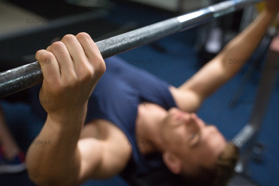 close up of man with barbell exercising in gym