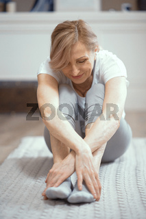 Cheerful mature woman relaxing after yoga exercises
