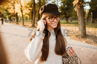 Beautiful young girl listening to music in the park through a wireless earpiece