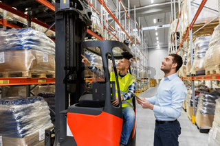 men with tablet pc and forklift at warehouse
