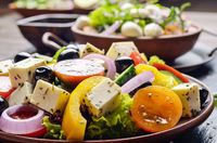 Mediterranean diet dish greek salad on slate tray with sauce aside