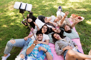 friends taking picture by selfie stick at picnic