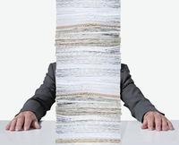 Person hinter einem Papierstapel.jpg