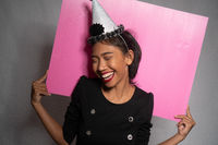 Pretty happy Asian girl in birthday cap holding pink board behind her isolated over gray wall