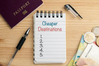 Saving traveling concept: notepad with copyspace to list cheaper destinations on wood table with a pen, a passport and some cash