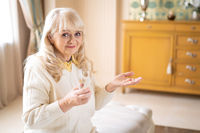 Senior woman holding pills and a glass of water