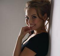 Lovely brunette in black dress smiling at camera