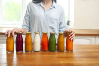 Diet nutrition with detox juice. Healthy woman posing with fresh juice bottles of  detox smoothie.