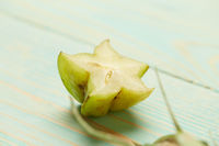 half fresh green carambola on a wooden background