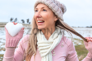 Exuberant woman holding a heart of snow