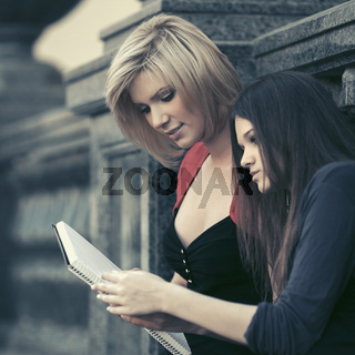 Two young fashion female students at university campus