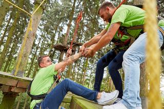 Team hilft Mann beim Klettern im Hochseilgarten
