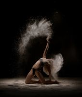 Young blonde dancing in white powder cloud