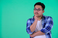 Young overweight Asian hipster man thinking and looking up