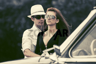 Happy young fashion couple next to vintage car