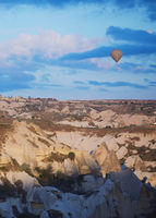 Hot air balloon flying over the rocks of Cappadocia