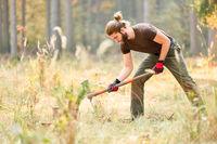 Waldarbeiter gräbt ein Loch für den Baum Setzling
