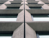 perspective view of geometric angular concrete windows on the facade of a modernist 1960s brutalist style building