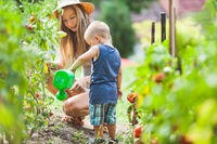 Cute toddler helphing out mom in the garden