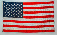 Worn american flag hanging from wall