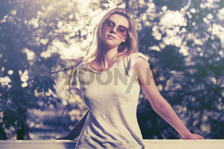 Young fashion blond woman wearing white top and sunglasses in city park