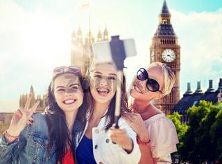group of smiling women taking selfie in london