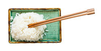 boiled rice with chopsticks on plate isolated