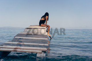 Attractive woman in a black swimsuit on the pier.