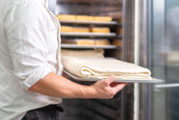 Pastry chef, putting the tray with dough into the fridge.