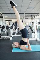 Frau auf der Yogamatte macht einen Nackenstand a