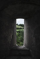 Nature view through an old stone window. Low light image