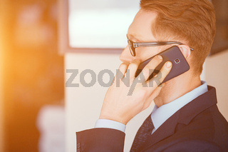 Smart businessman talking on the phone in sunny office