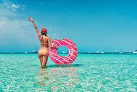 Young woman in bikini with pink donut swim ring in the sea