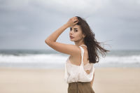 Lifestyle portrait of happy carefree woman walking on the beach with space for text.