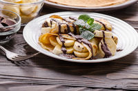 French crepes with chocolate sauce and banana in ceramic dish on wooden kitchen table