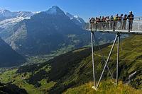 Aussichtsplattform mit Touristen hoch über dem Ort Grindelwald