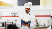happy indian chef reading cookbook at kitchen