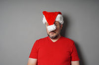 christmas hater hiding face behind santa hat