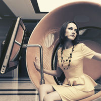 Young fashion business woman sitting on computer chair in office