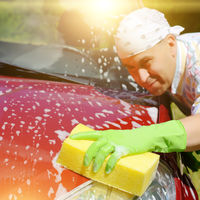 Man in green gloves washing car with yellow sponge
